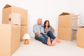 Couple at new home happy mature sitting on the floor in their boxes lamp and carpet in background Stock Photography