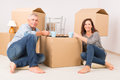 Couple at new home happy mature sitting on the floor in their and drinking coffee or tee boxes in background Royalty Free Stock Image