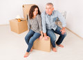 Couple at new home happy mature unpacking boxes in their Stock Photography