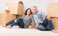 Couple at new home happy mature unpacking boxes in their Royalty Free Stock Photo