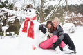 Couple Next To Snowman With Hot Drink Royalty Free Stock Images