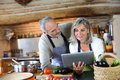Couple in old kitchen looking for recipe on internet senior home at tablet Stock Image