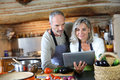 Couple in old kitchen looking for recipe senior home at tablet Stock Photography