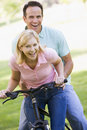 Couple on one bike outdoors smiling Stock Image