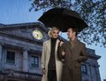 Couple outdoors elegant with umbrella against building facade Stock Photos