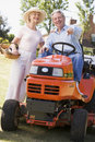 Couple outdoors with tools and lawnmower pointing Stock Photography