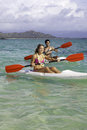 Couple paddling surfskis in hawaii Royalty Free Stock Image