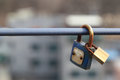 Couple padlocks are locked on rail with blurred city background, everlasting friendship symbol or forever love concept Royalty Free Stock Photo
