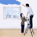 Couple painting new room in blue color Stock Image