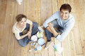 Couple with painting tools sitting on wooden floor high angle portrait of happy Stock Image
