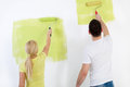 Couple painting wall at home young in green back view Royalty Free Stock Photo