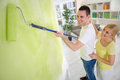 Couple painting wall with paint roller together Stock Photos