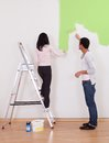Couple painting the wall portrait of young in apartment Royalty Free Stock Photo