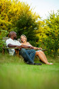 Couple at the park interracial sitting in adirondack chairs in summer Royalty Free Stock Photography