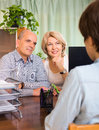 Couple of pensioners talking with employee at office Stock Photography