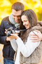Couple with photo camera in autumn park summer holidays vacation travel tourism happy people dating concept Royalty Free Stock Photos