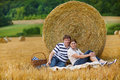 Couple picnicking on yellow hay field on summer evening young Stock Image