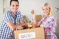 Couple with piggy bank and keys with moving boxes concept saving Royalty Free Stock Photo