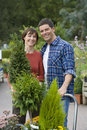 Couple with plants in garden center, smiling, portrait Royalty Free Stock Photo
