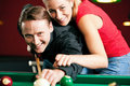 Couple playing billiards Stock Photos