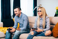 Couple playing computer games and video games on console while sitting on sofa at new home