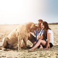 Couple playing with dog on the beach photo of of a Royalty Free Stock Photo