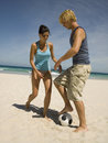 Couple playing football on the beach a sandy Stock Images