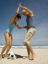 Couple playing football on the beach a sandy Stock Photo