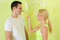 Couple playing with paint brush young girl painting nose her boyfriend Stock Image
