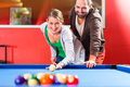 Couple playing pool billiard game or friends with queue and balls on table Stock Photos