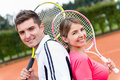 Couple playing tennis portrait of a and holding rackets Royalty Free Stock Image