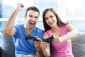 Couple playing video games excited on the sofa Stock Photography