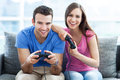 Couple playing video games on the sofa Stock Images