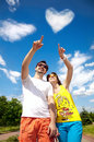 Couple pointing at cloud heart Royalty Free Stock Photo