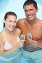 Couple in pool drinking sparkling Royalty Free Stock Photos