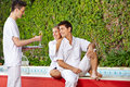 Couple at pool getting champagne from waiter happy sitting the a Royalty Free Stock Photo