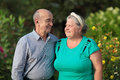 Couple portrait of an elderly on the background of green branches of trees Stock Photo
