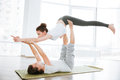 Couple practicing acro yoga on green mat in studio together Royalty Free Stock Photo