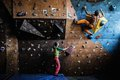 Couple practicing rock climbing on a rock wall muscular men indoors Royalty Free Stock Photography