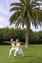 Couple practicing yoga in park full length of middle aged Stock Images