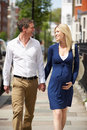 Couple with pregnant wife walking along urban sidewalk chatting to each other smiling Royalty Free Stock Photo