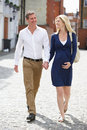 Couple with pregnant wife walking along urban sidewalk in daylight smiling Stock Photos