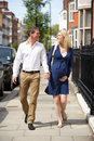 Couple with pregnant wife walking along urban sidewalk holding hands smiling to each other Royalty Free Stock Photos