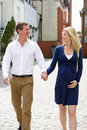 Couple with pregnant wife walking along urban sidewalk looking at each other holding hands Stock Photos