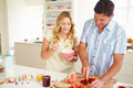Couple preparing healthy breakfast in kitchen happy together cutting fruit Stock Image