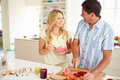 Couple preparing healthy breakfast in kitchen looking at each other smiling Royalty Free Stock Photos