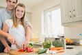 Couple preparing a salad in kitchen Stock Photos