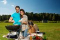 Couple preparing sausages outdoors young on a grill Stock Image