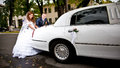 Couple pushing white wedding limousine newly married Stock Photo