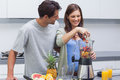 Couple putting fruits into blender various Royalty Free Stock Images
